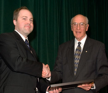 Bernard Langer (right) presents the Bernard Langer Surgeon Scientist Award to Michael Taylor (NeurSurg)